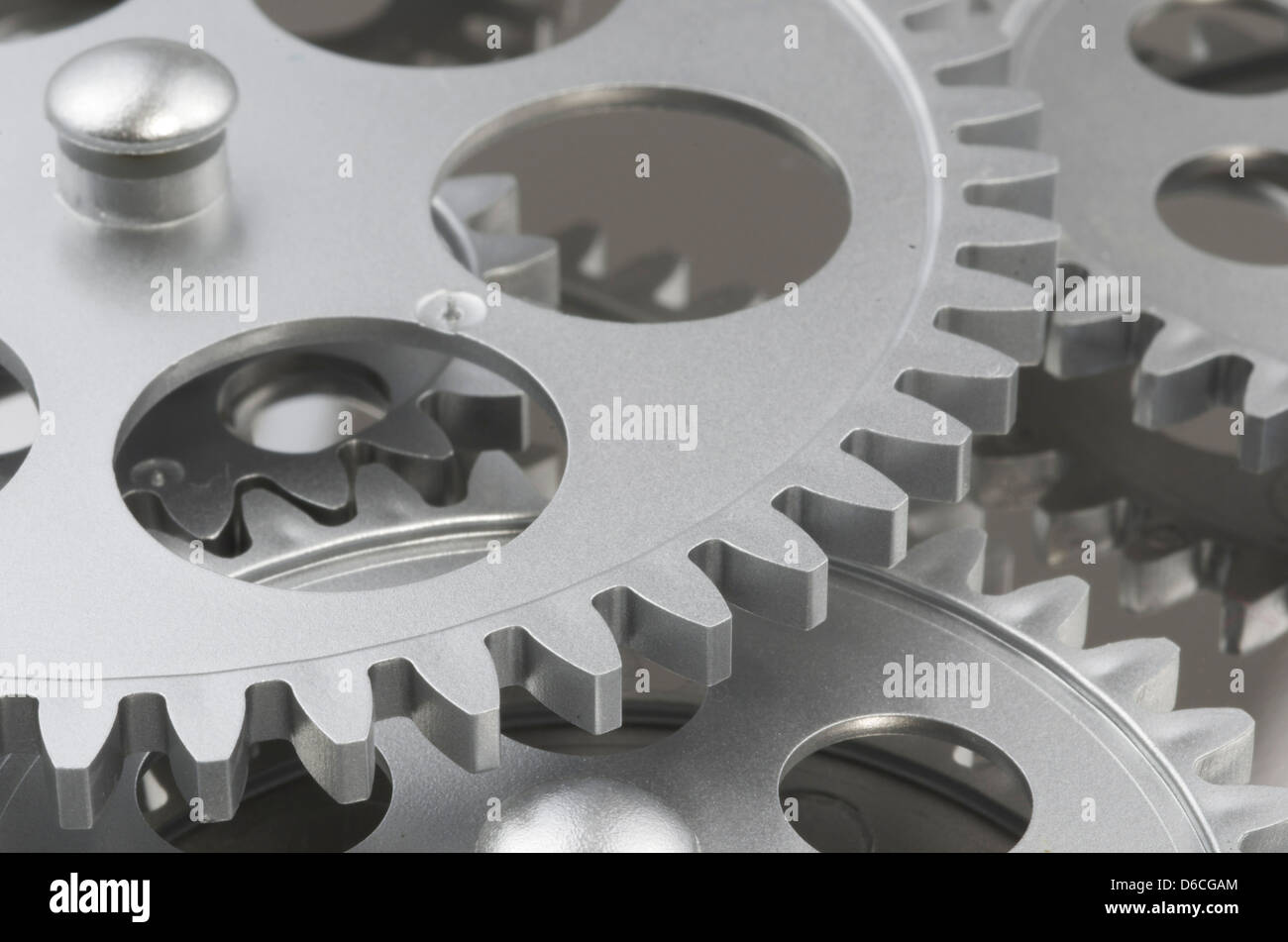 Close up of gray gears layered and interlocked. - Stock Image