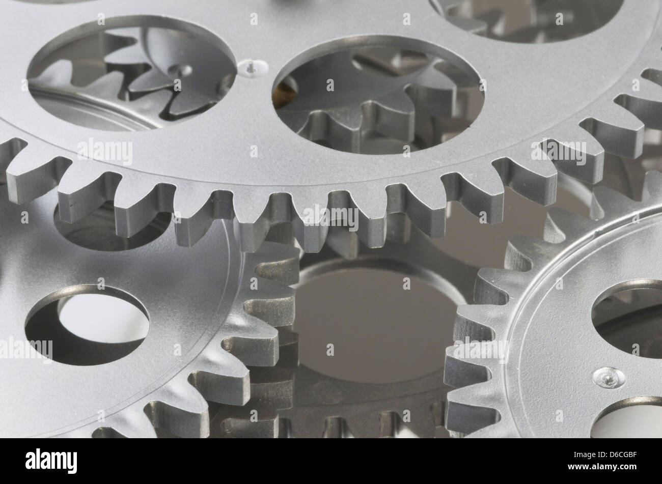 Close up of gray gears layered and interlocked - Stock Image