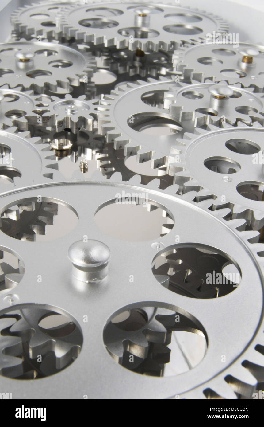 Many silver gears interlocked and working together. - Stock Image