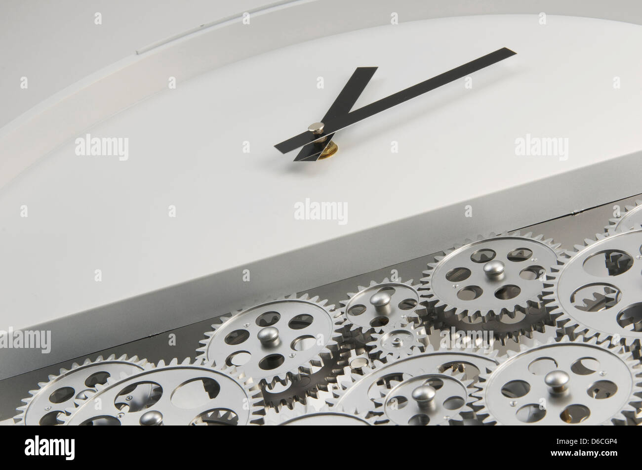 Slanted shot of a white faced clock with black hands and gears showing in it's lower half. - Stock Image