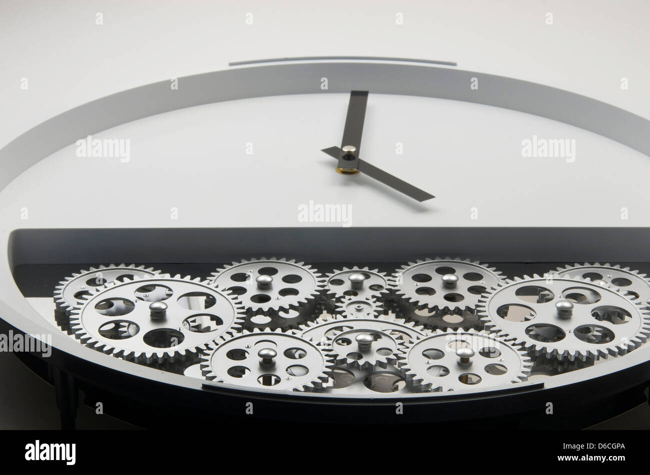 White modern looking clock with black hands and gears in it's lower half which make the clock tick. - Stock Image