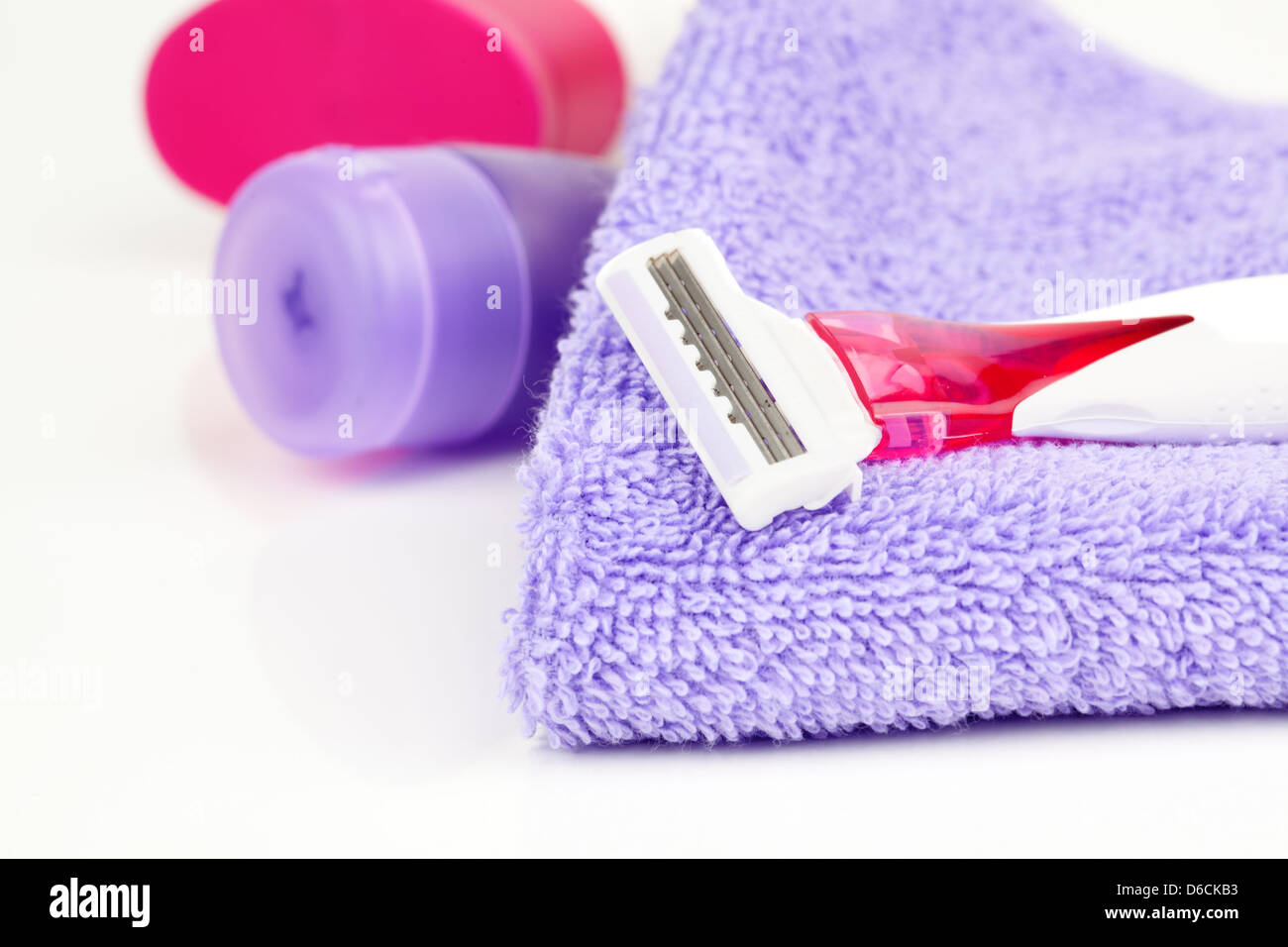 Closeup of pink shaving blade on towel with moisturizer - Stock Image
