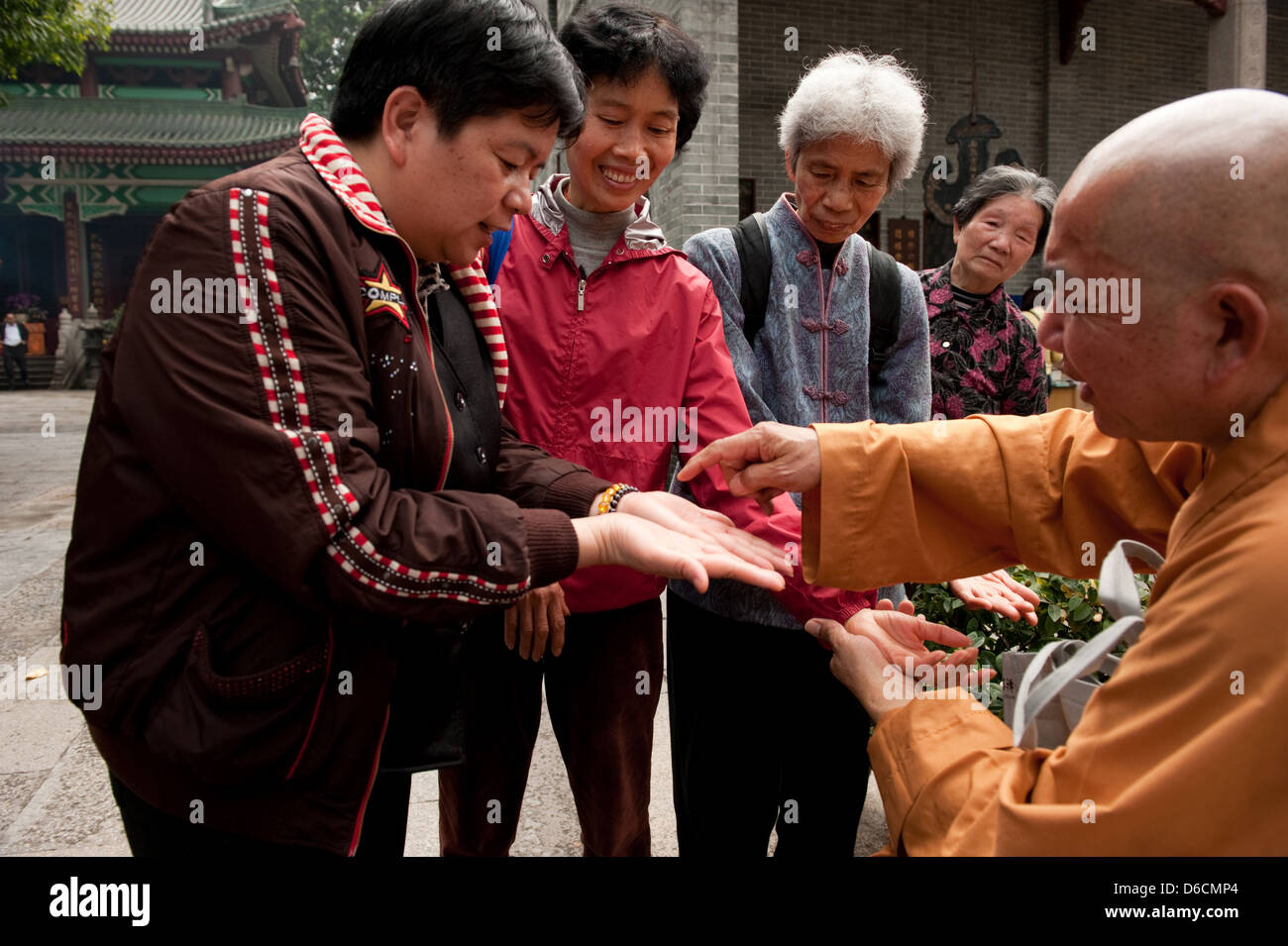 Guangzhou, China, is a monk acupressure with visitors in Filial Piety Temple Stock Photo