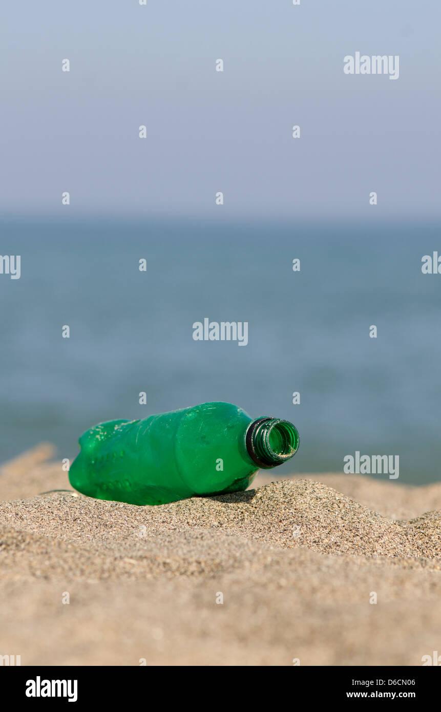 Plastic green bottle on the beach, Spain. - Stock Image