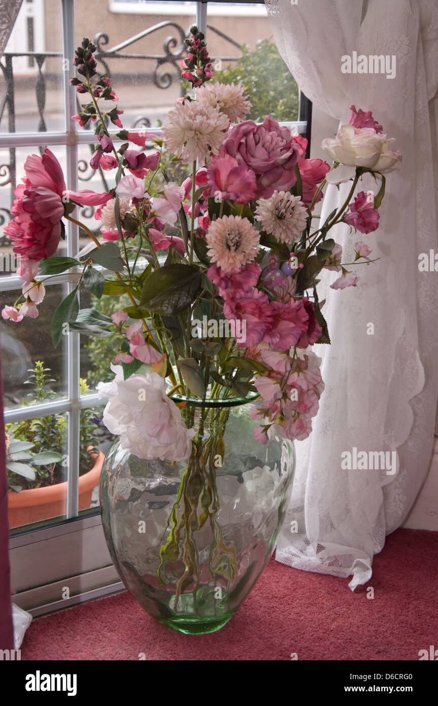 Artificial Flowers Displayed In Large Glass Vase Floor Standing In
