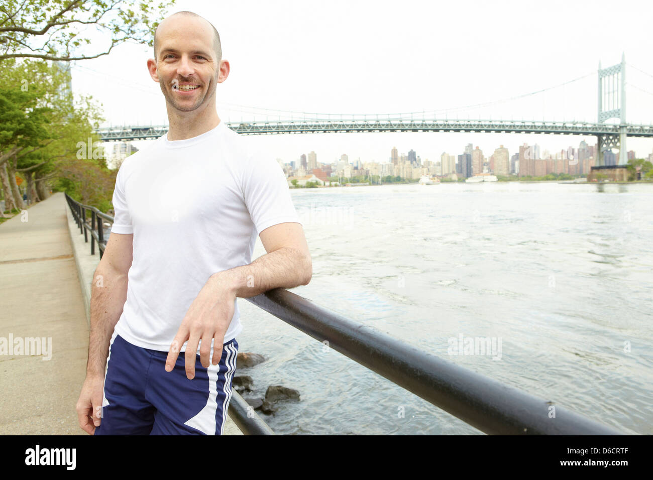 Man leaning by side railing next to river with bridge in background - Stock Image