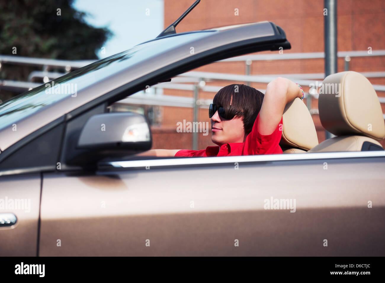 Young man driving a convertible car - Stock Image