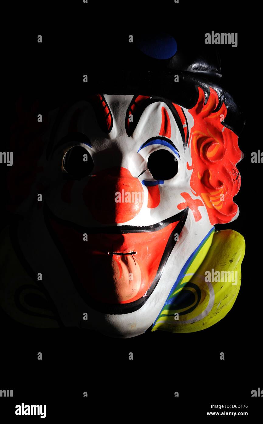Clown mask hiding something menacing. - Stock Image