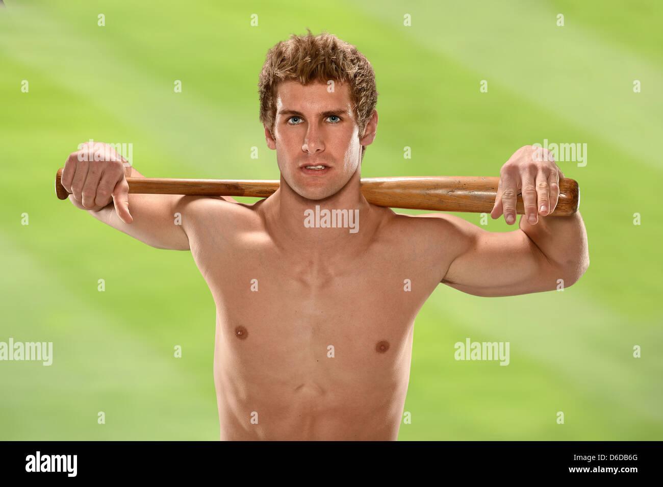Shirtless man holding baseball bat outdoors - Stock Image