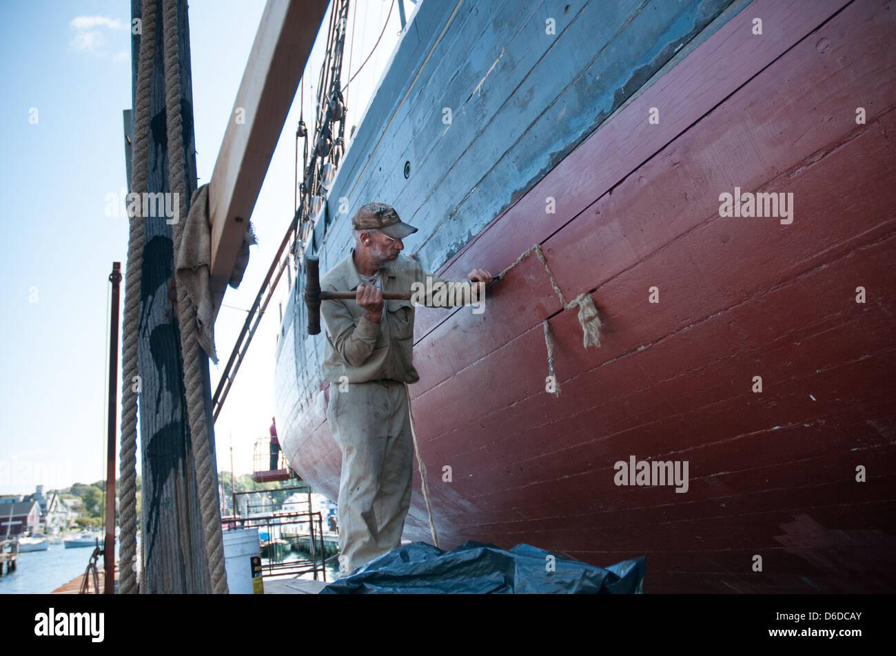 A shipyard worker hammers 'oakum' between the wooden boards in the hull of Schooner Highlander Sea. - Stock Image