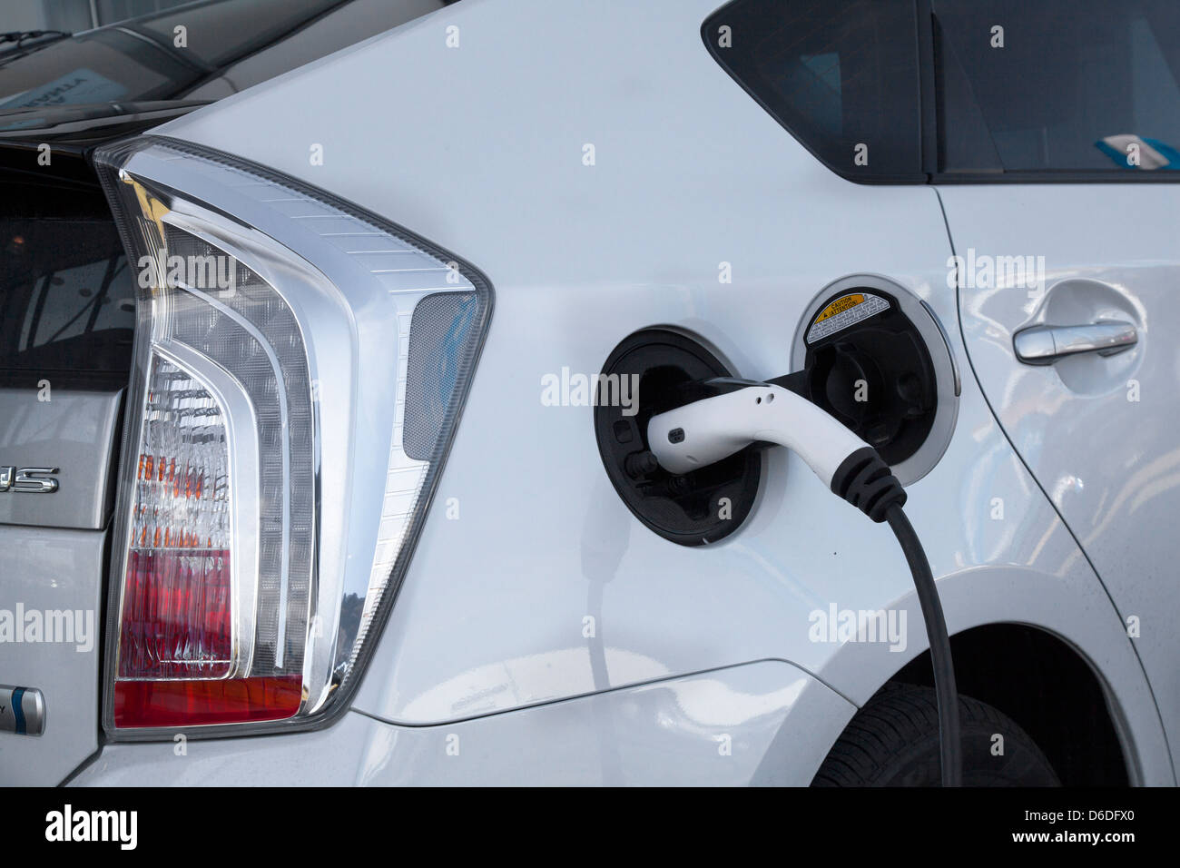 Toyota Prius PHEV Recharging _White Toyota Prius Car being charged at Preston Showrooms, Lancashire, UK - Stock Image