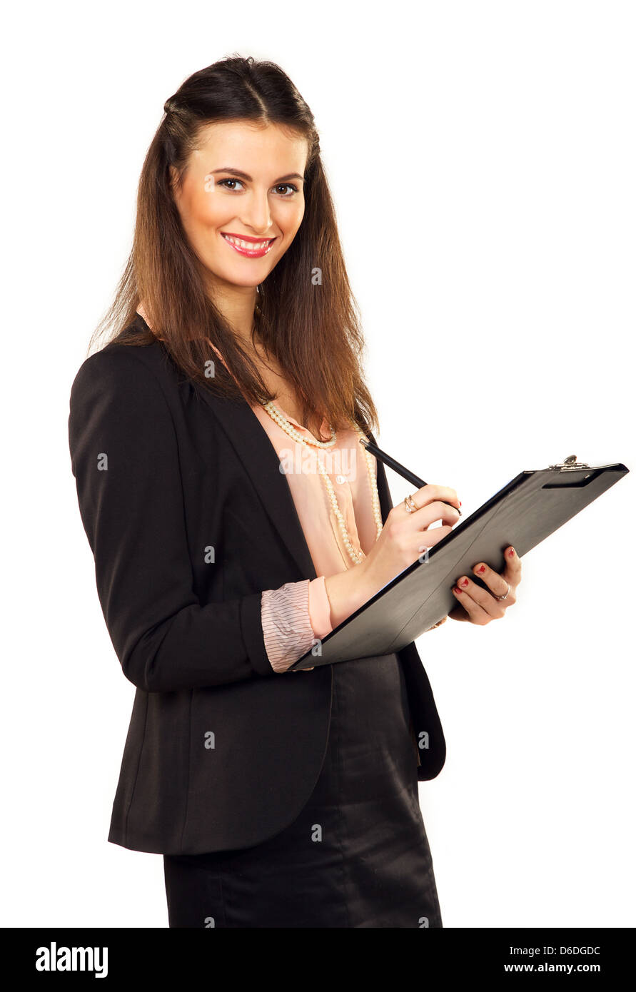 Portrait of a female professional smiling while writing on clipboard - Stock Image