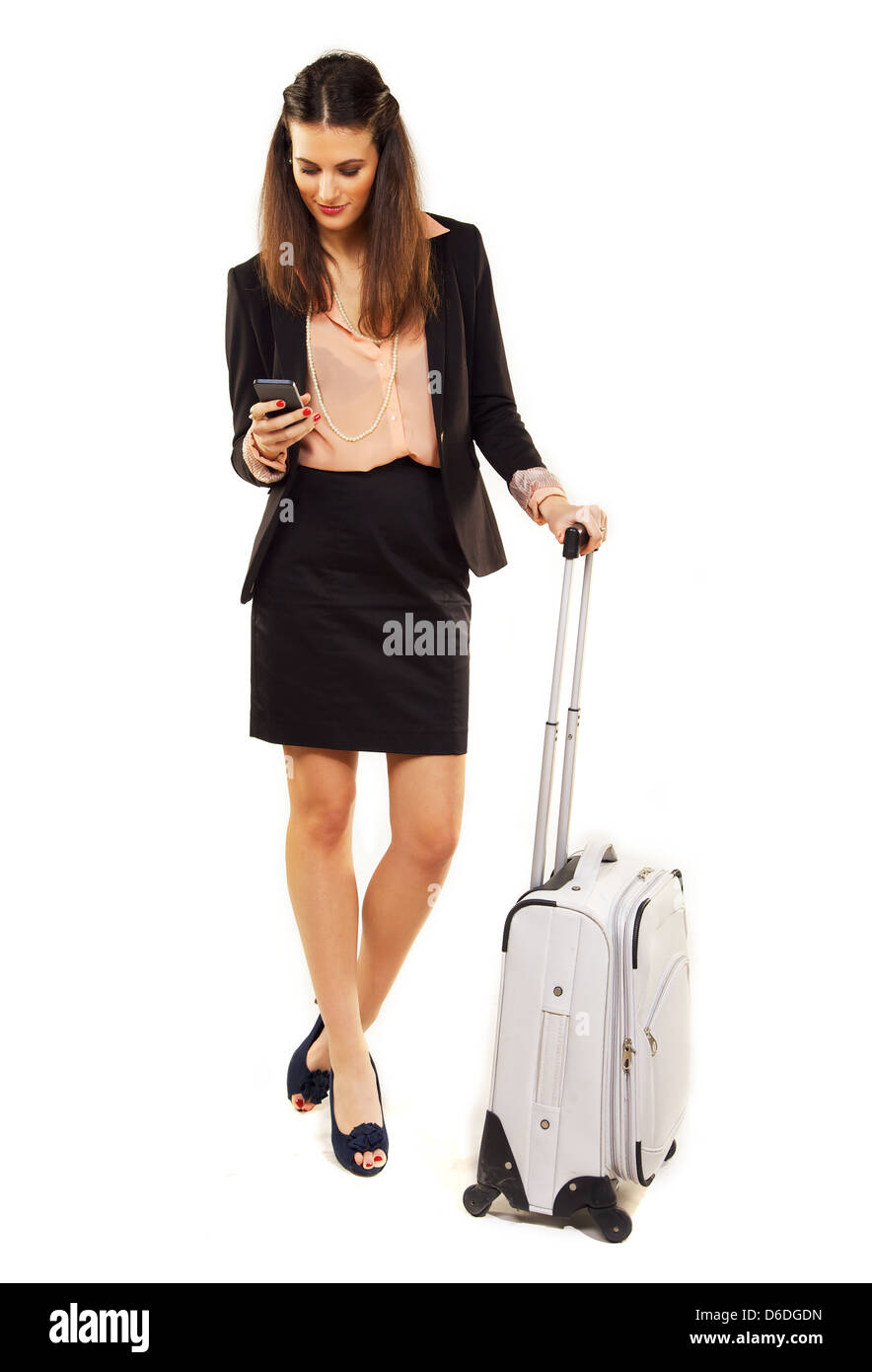 Woman on business trip reading text messages on her cellphone - Stock Image