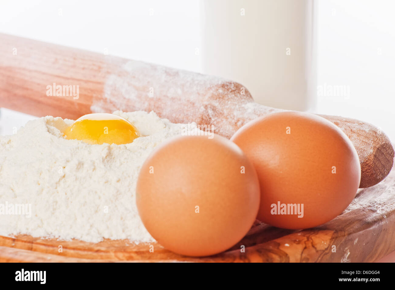 Vintage rolling pin with flour and eggs. Country still life images with soft lighting and small degrees of freedom - Stock Image
