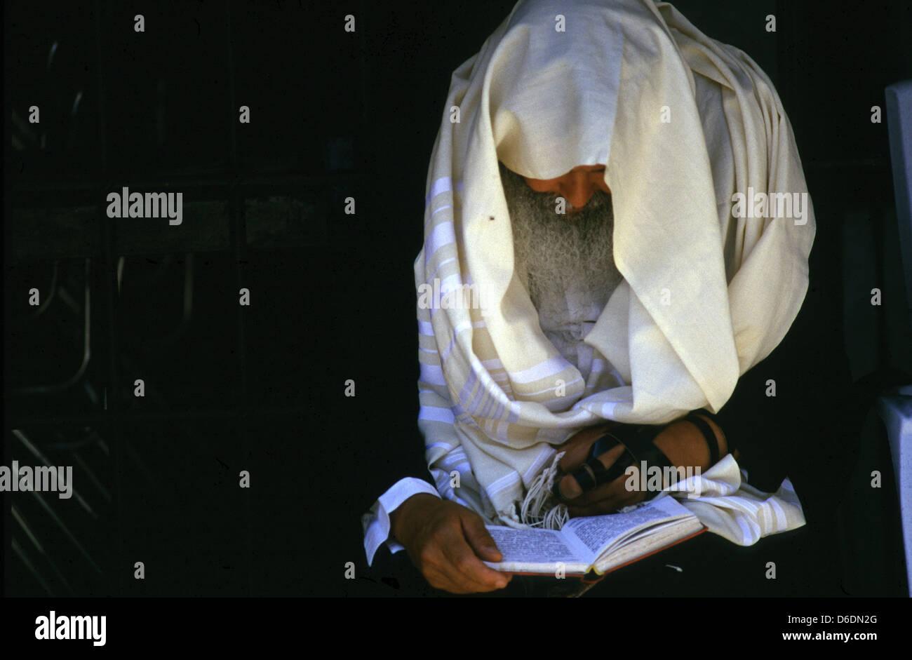 Orthodox Jewish man wrapped with a tfilin and talit prayer shawl reading the Siddur Jewish book of pray - Stock Image