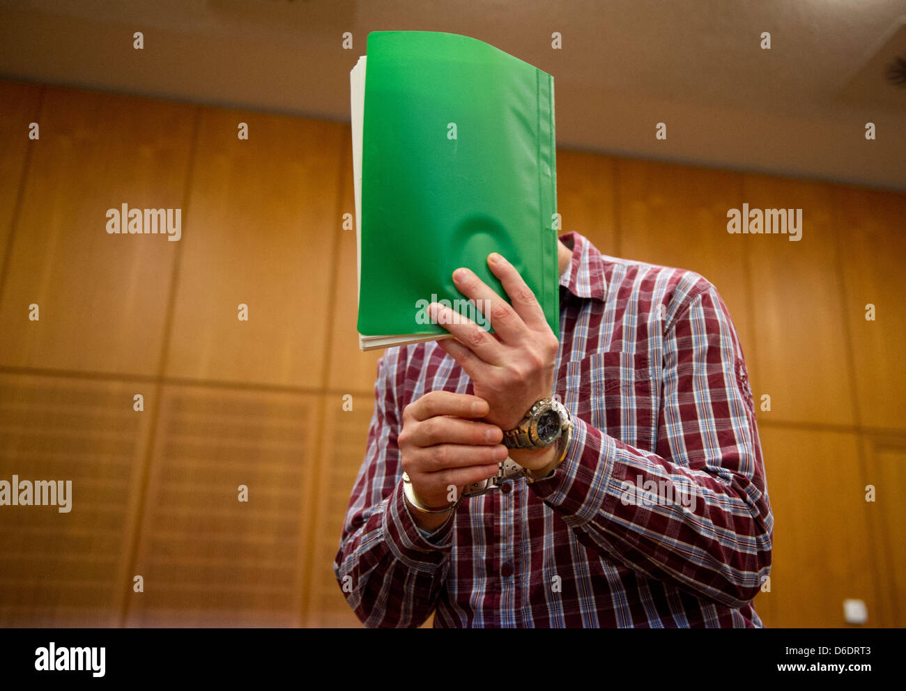 Bus hijacker Thomas Feldmann hides his face behind files at the start of his trial in a high-security court room Stock Photo