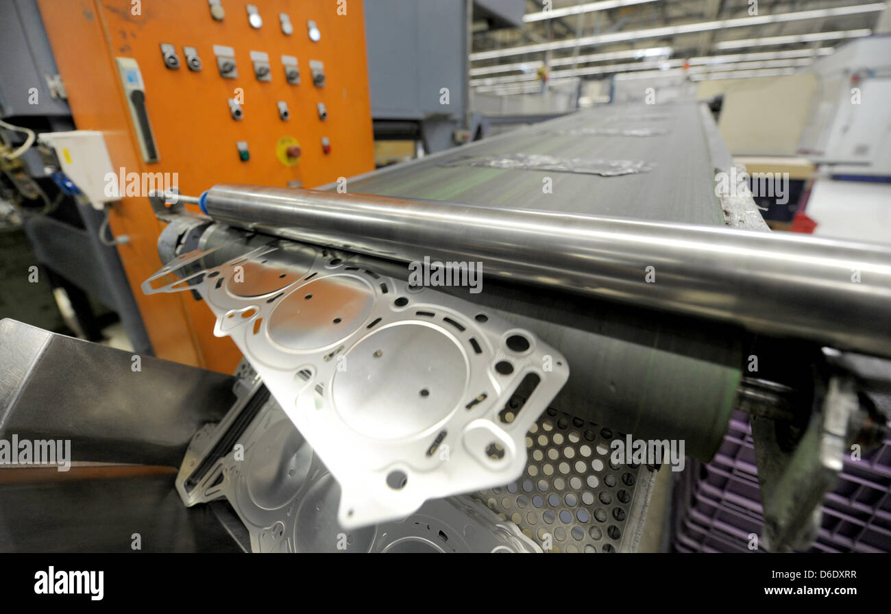 A cylinder head gasket falls off an assembly line at the