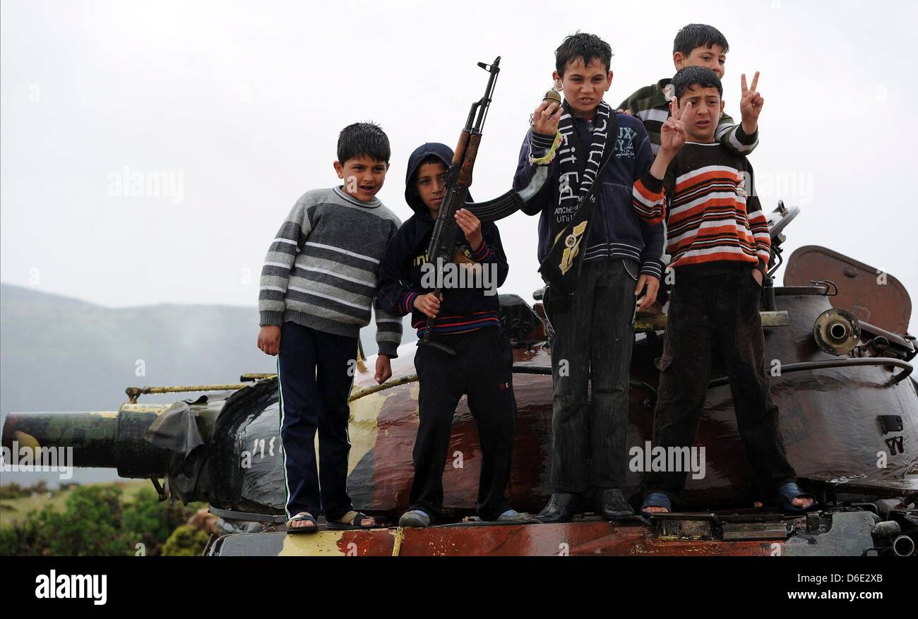 DARKOUSH, SYRIA: Syrian kids holding an assault rifle while standing on top of a tanker on April 16, 2013, in Darkoush, Stock Photo