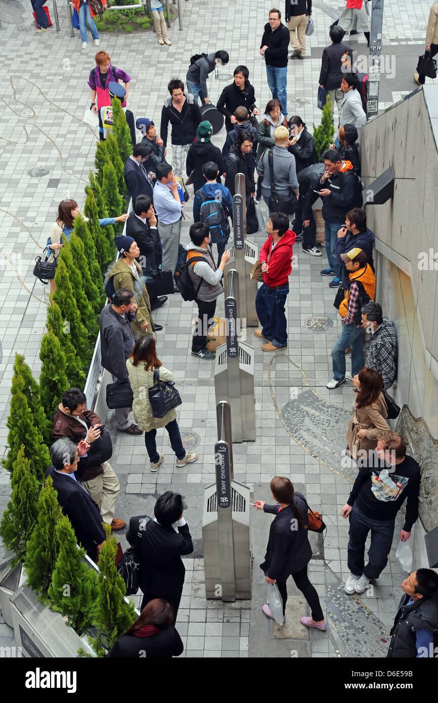 Outdoor smoking area with people smoking cigarettes in the street in Shinjuku, Tokyo, Japan Stock Photo