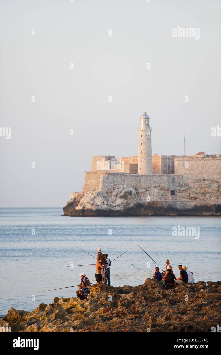 people fishing on the Malecon, lighthouse on El Morro, Havana, Cuba, West Indies, The Caribbean - Stock Image