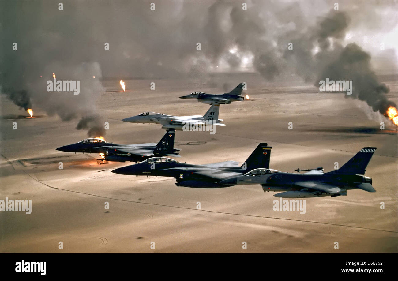 US and Saudi Arabian Air Force F-16A, F-15C and F-15E fighter aircraft fly over burning oil wells during operation - Stock Image
