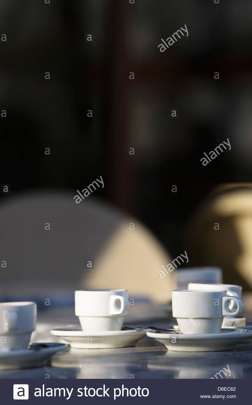 Several white coffee cups saucers cafe table Paris France - Stock Image