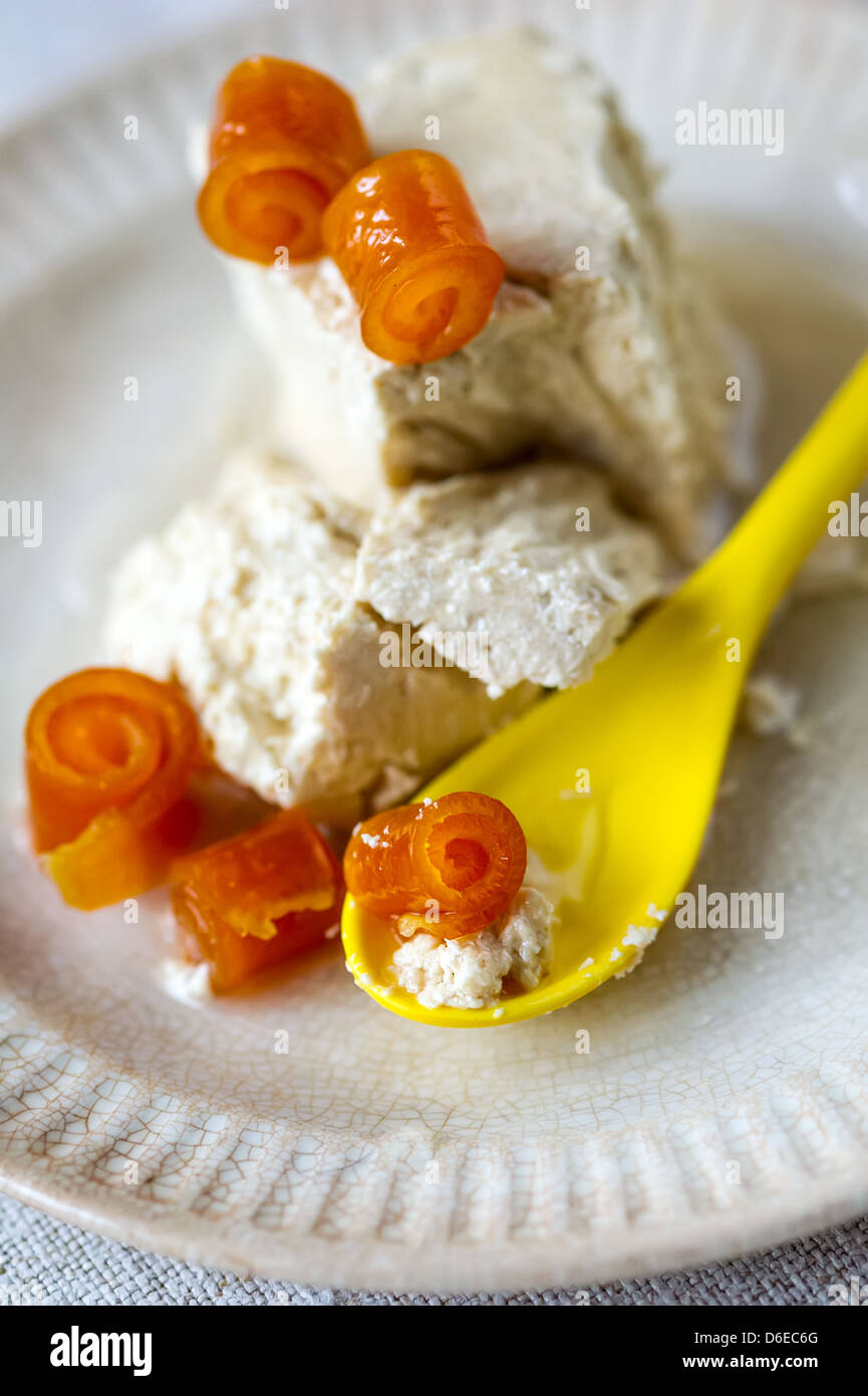 Sweet halva with twisted orange peels and yellow spoon on a plate - Stock Image