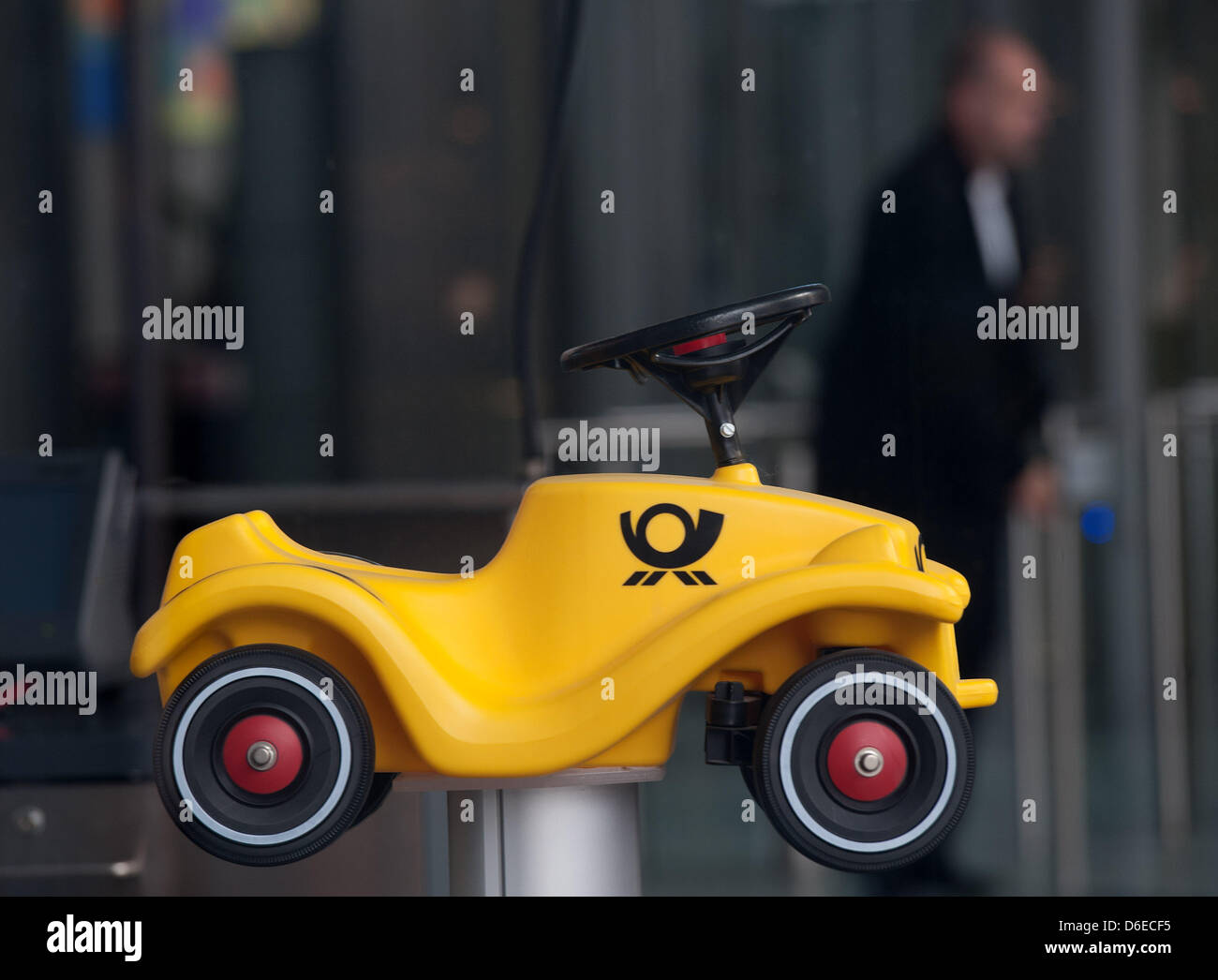 A bobbycar with the logo of the post on it sits in the entrance of the headquarter of the Deutsche Post AG in Bonn, - Stock Image
