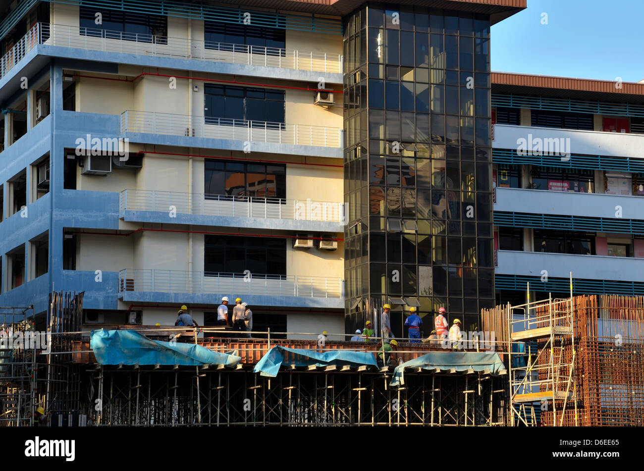 Building construction site with foreman and hard hat workers - Stock Image
