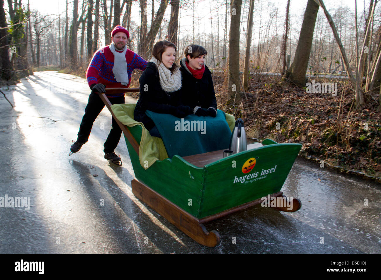 Mandy and Christin take a tour on a frozen stream with a sled pushed by Hagen Conrad in Burg, Germany, 31 January - Stock Image
