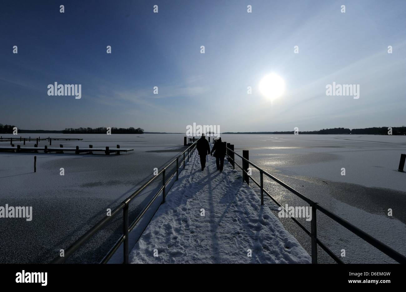 People walk on a jetty at Lake Ploen in Ploen, Germany, 05 February 2012. The sunny but chilly weather made many - Stock Image