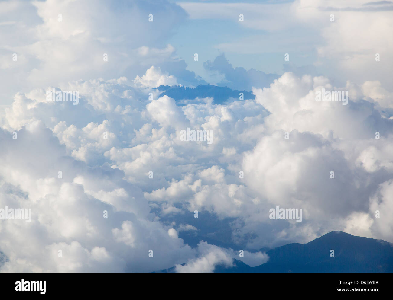 The jagged peaks of the summit of distant Gunung Kinabalu pushing through cloud Sabah Borneo - Stock Image