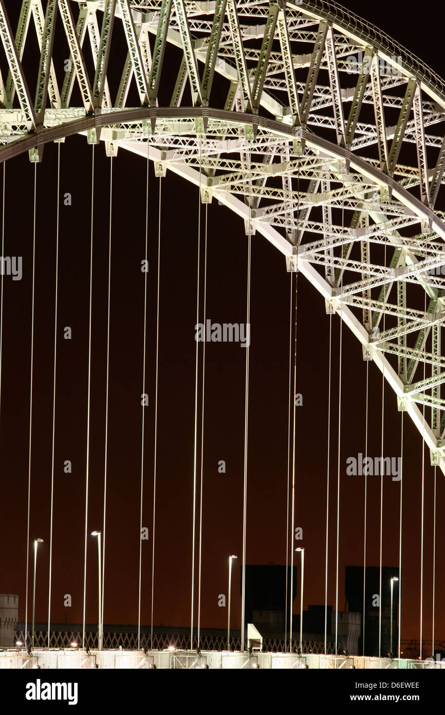 The Runcorn or Silver Jubilee Bridge over the River Mersey and Manchester Ship Canal, Runcorn, Cheshire, illuminated - Stock Image