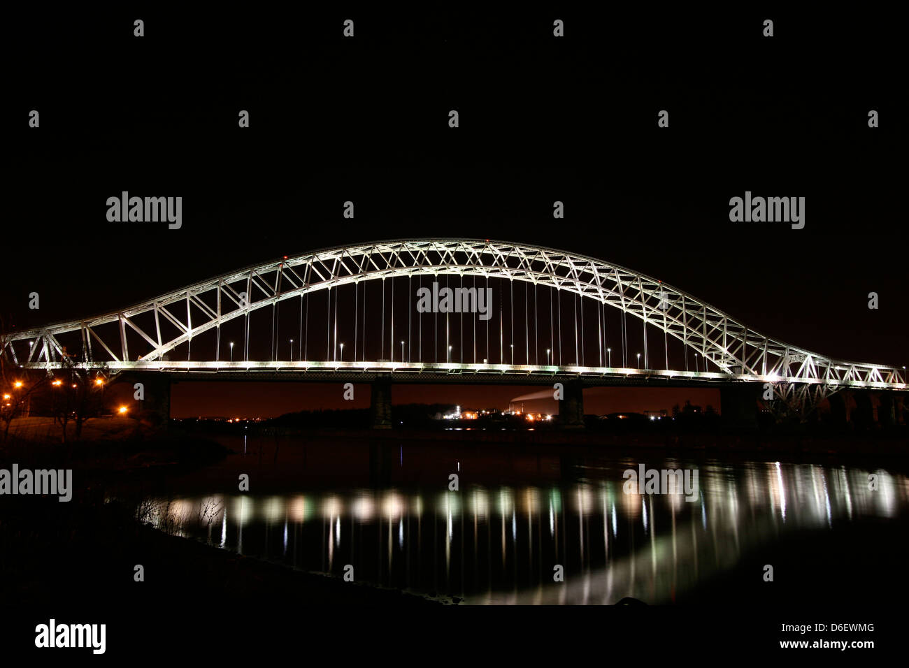 Runcorn, or Silver Jubilee Bridge over River Mersey and Manchester Ship Canal, Runcorn, Cheshire, England illuminated - Stock Image