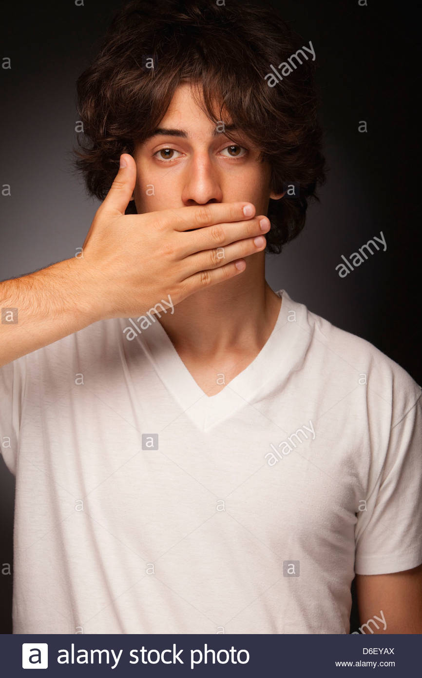 Teenager hand covering mouth silence censorship - Stock Image