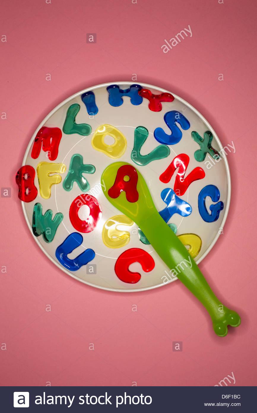 Alphabet soup bowl multicolored letter bowl spoon - Stock Image