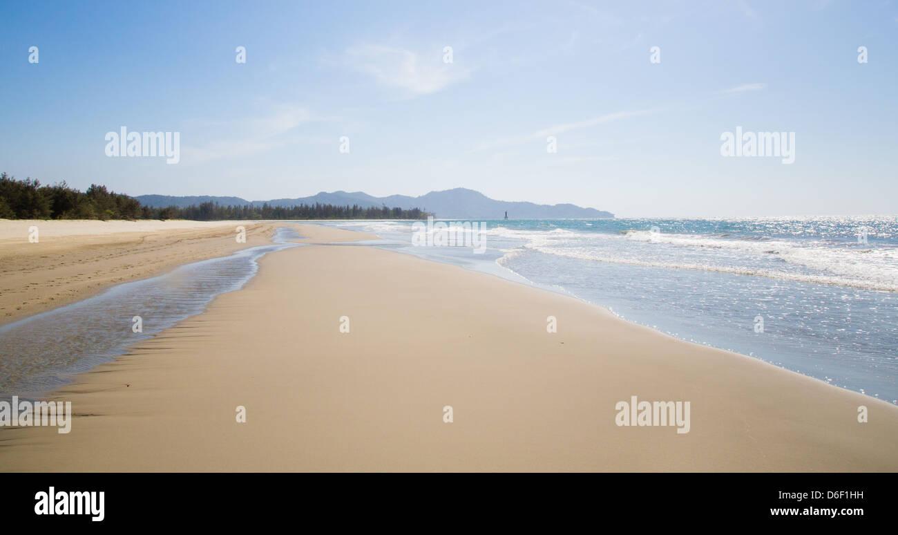 Wide deserted white sand beach at Rasa Ria near Kota Kinabalu in Malaysian Borneo bordering the South China Sea - Stock Image