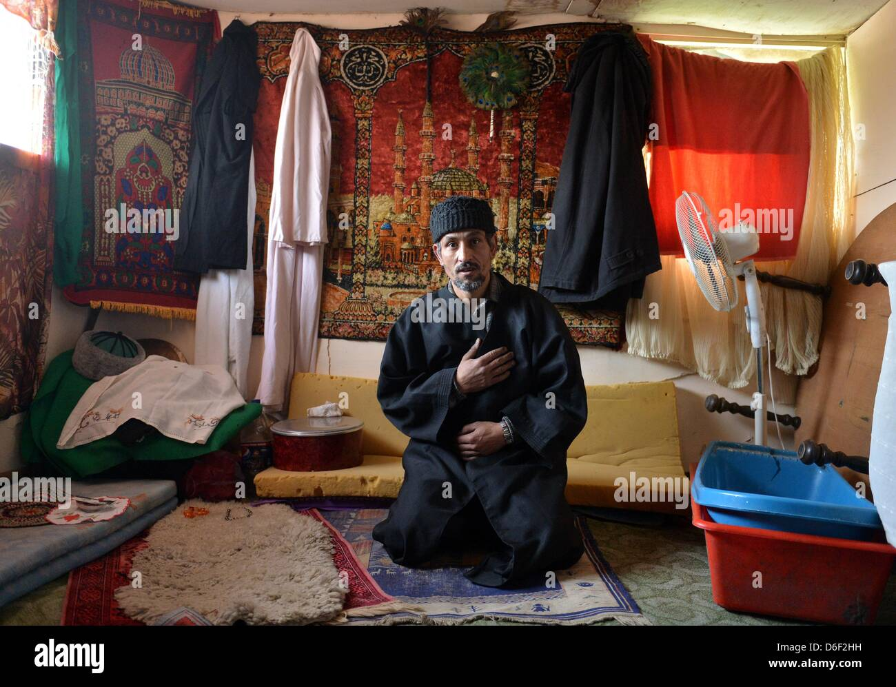 Gashijani kneels on a carpet for prayer his makeshift house in the Belvil settlement, which is inhabited by local - Stock Image