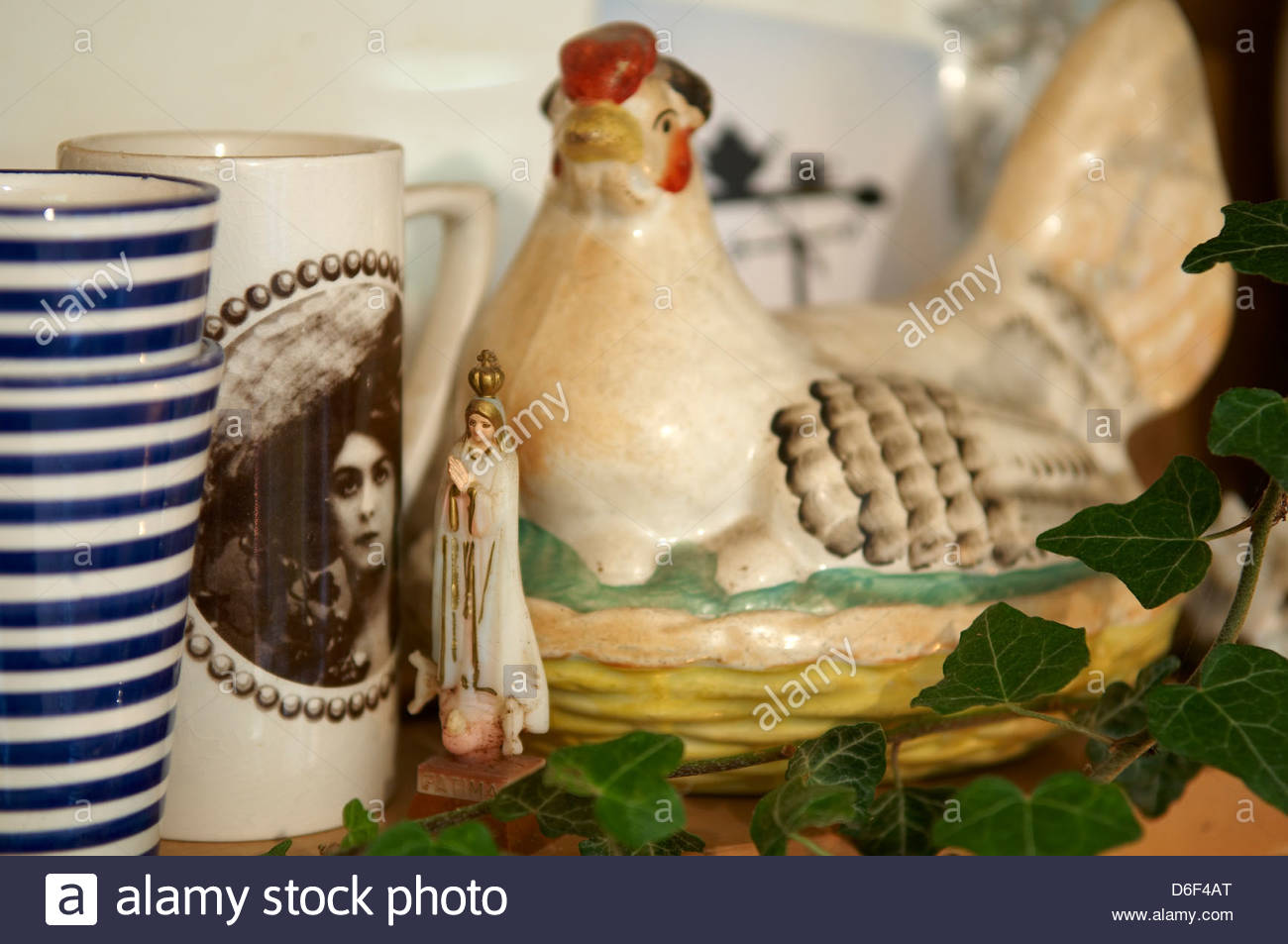 Mugs and a  Chicken shaped egg dish, sitting on the shelf - Stock Image