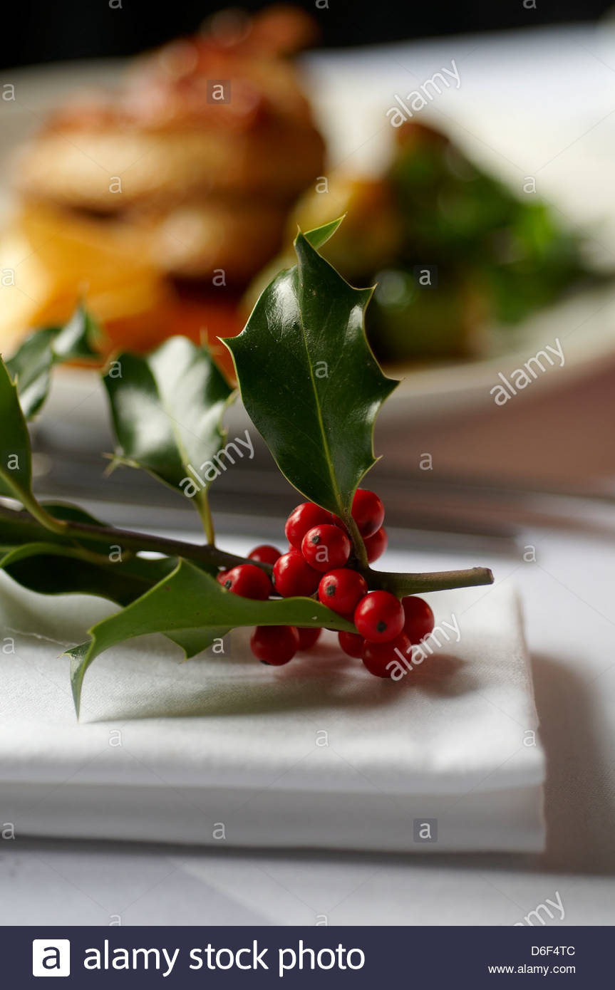 Decorative piece of holly on a restaurant table with food in the background - Stock Image
