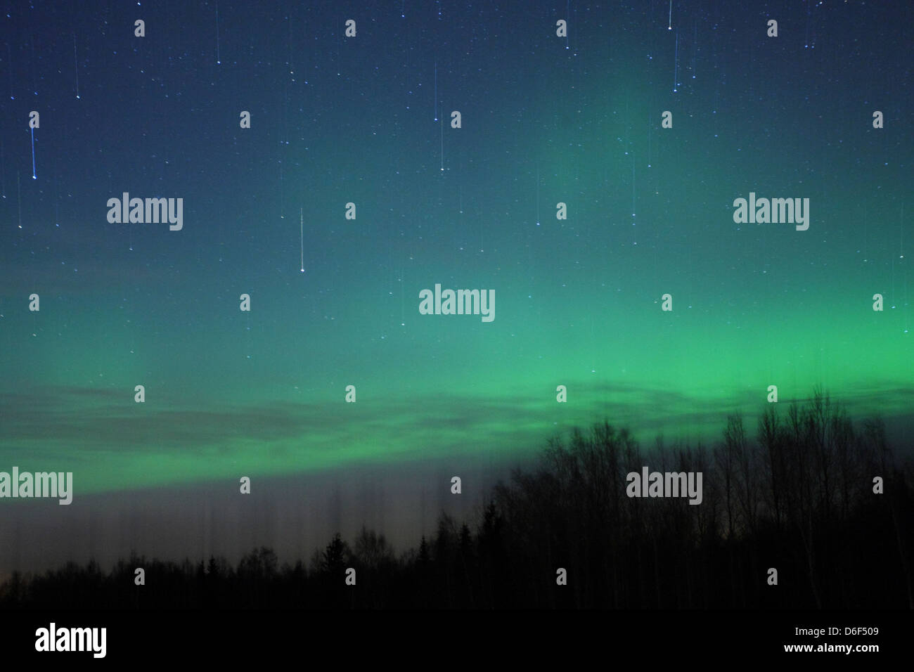 Falling stars and Northern lights (Aurora Borealis) in the sky. Europe, Estonia Stock Photo