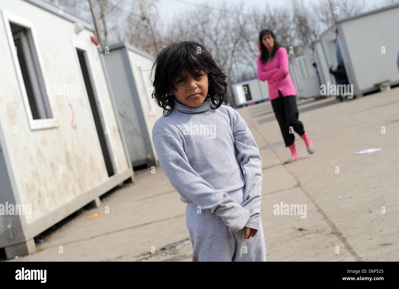 A girl stands between container houses in the Makis settlement, which is inhabited by local Roma in Belgrade, Serbia, - Stock Image