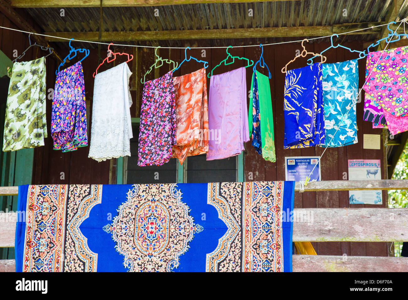 Gaily patterned fabrics hung out on coloured clothes hangers on a washing line in Sukau on the Kinabatangan River - Stock Image