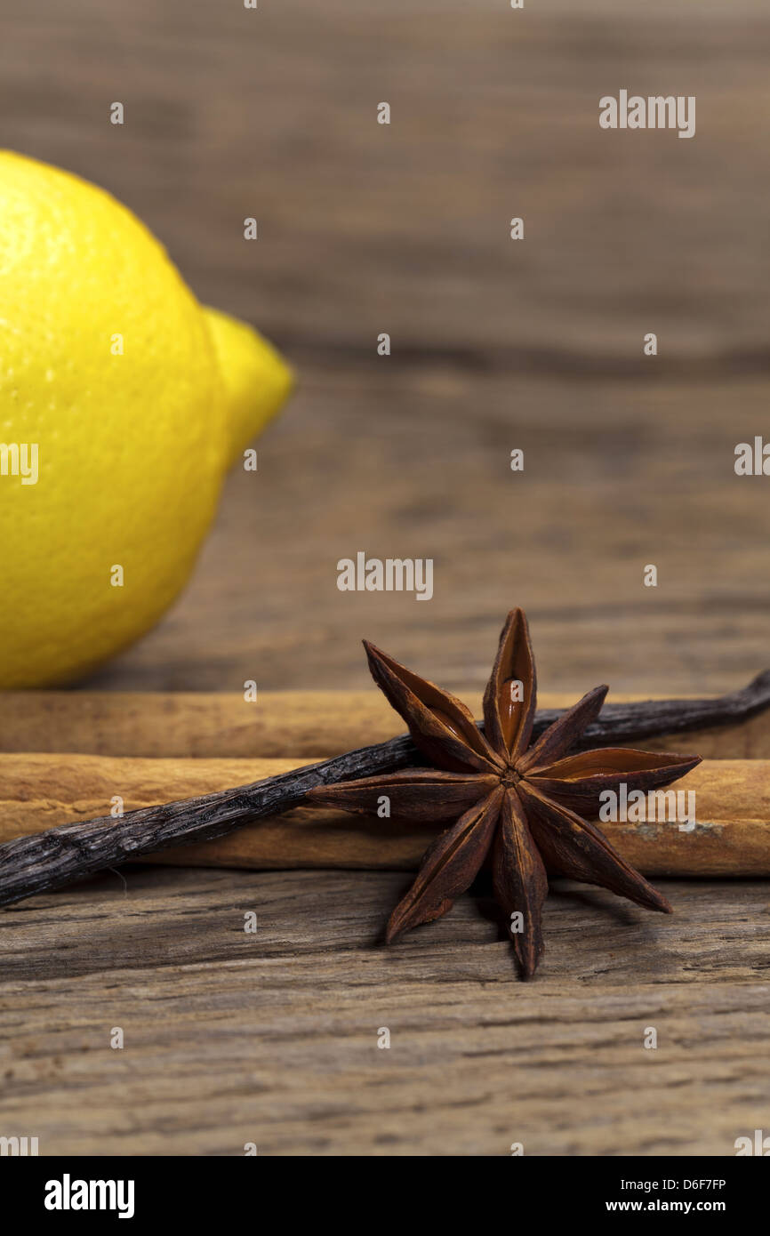 Cinnamon sticks, star anise and vanilla pod and a lemon in the background on a rustic wooden board - Stock Image