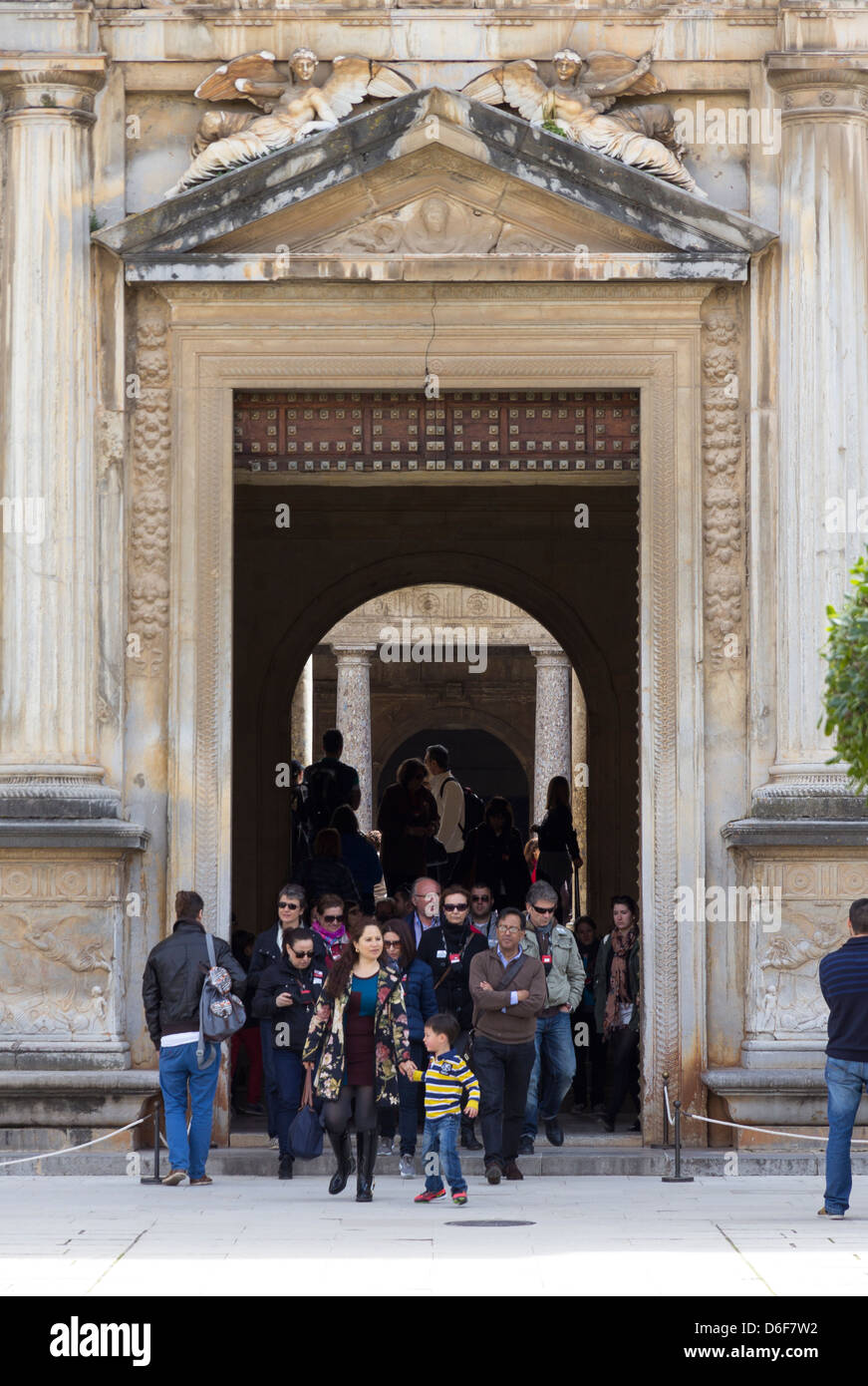 A crowd of tourists emerge from the entrance to Palacio de Carlos V, Alhambra, Granada - Stock Image