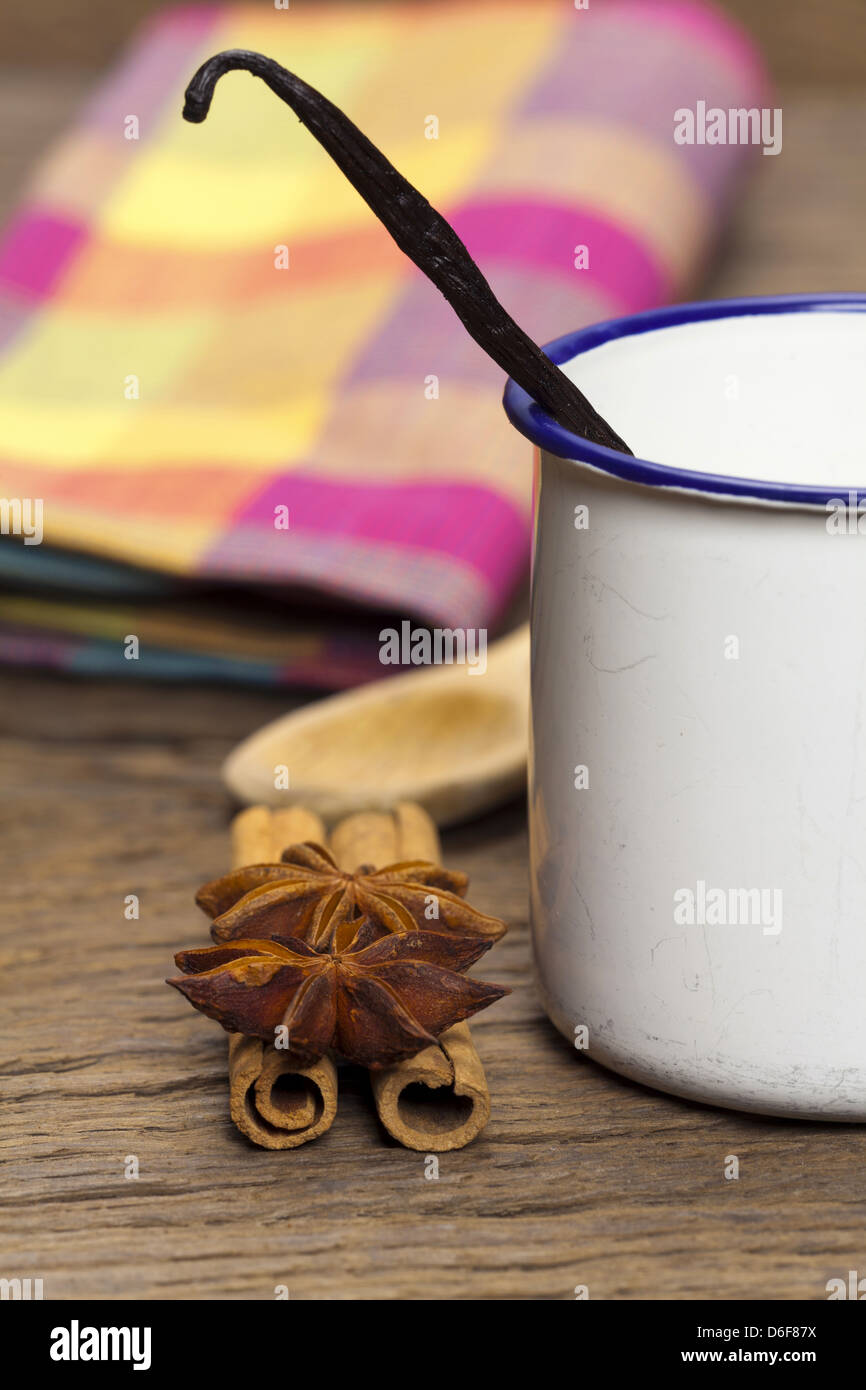 Cinnamon sticks, star anise and vanilla pod in an enamel cup on rustic wooden board - Stock Image