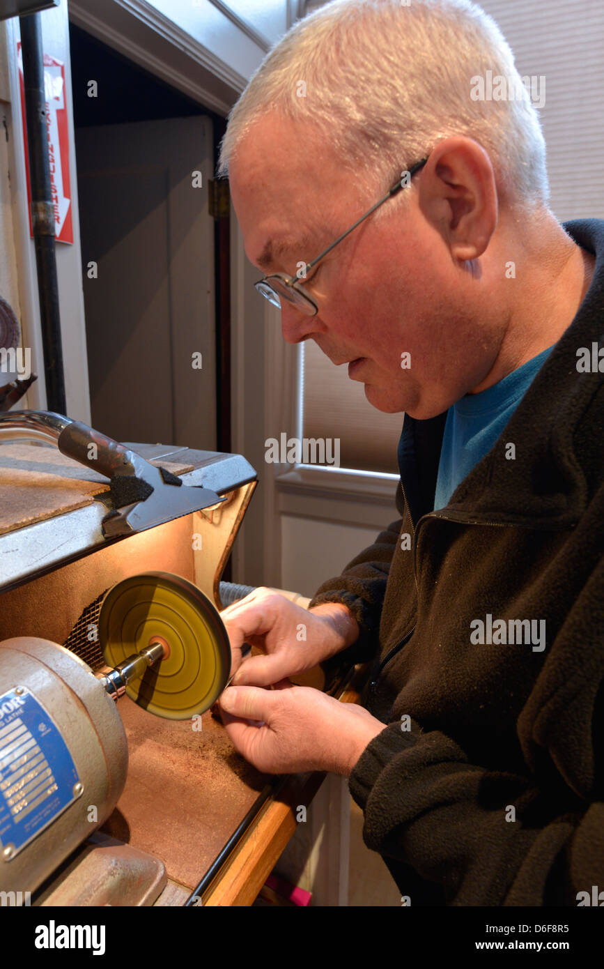 Jeweler polishing a piece of jewelry on a motorized lathe, Joseph, Oregon. - Stock Image