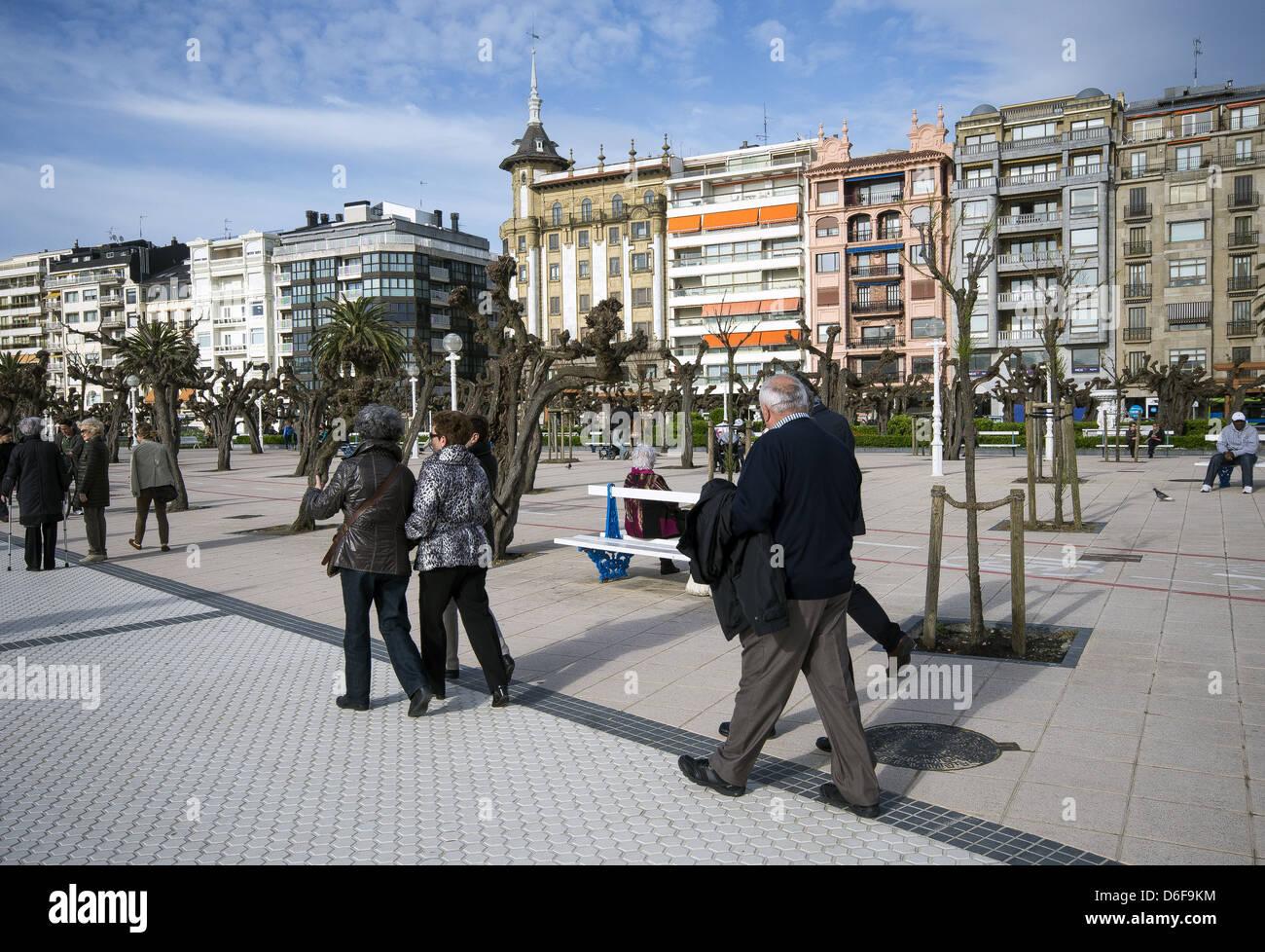 Tourist walking along the seafront in San Sebastián, Donostia, Basque Country, Spain - Stock Image