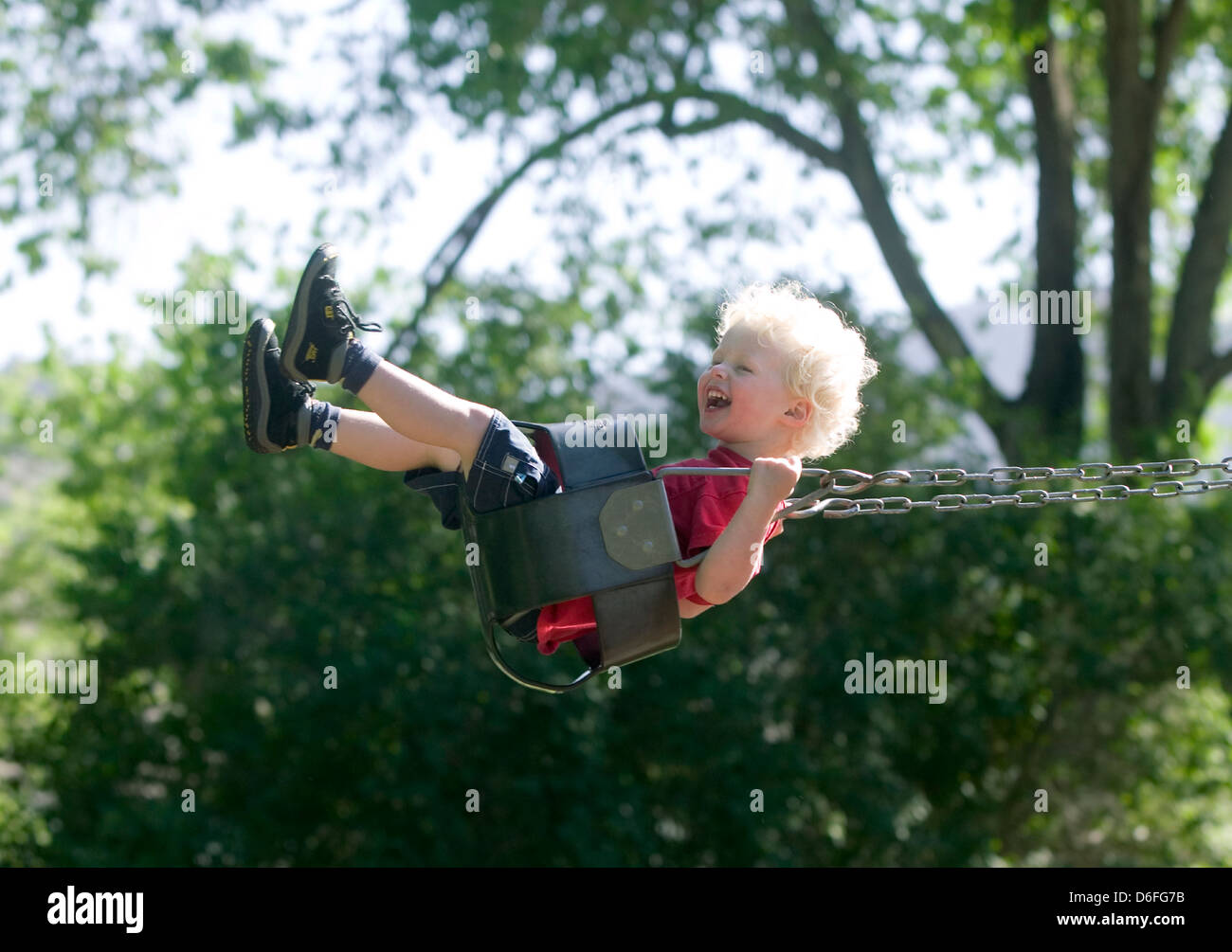 Blonde haired boy swinging on a swing on the playground. - Stock Image