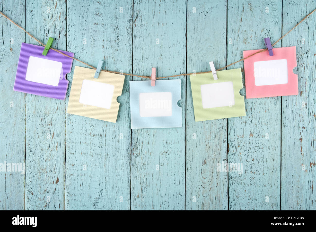 Five empty colorful photo frames or notes paper hanging with clothespins on wooden blue vintage shabby chic background - Stock Image